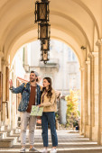 Selective focus of boyfriend pointing with hand and girlfriend with map excited and surprised in city