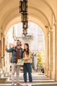 Selektivní zaměření přítele ukazuje rukou a přítelkyně s mapou vzrušený a překvapený ve městě