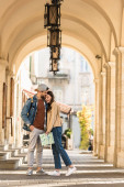 Selective focus of boyfriend with hand in pocket hugging girlfriend with map in city