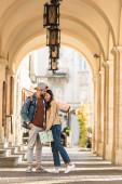 Selektivní zaměření přítele s rukou v kapse objímání přítelkyně s mapou ve městě