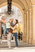 Selective focus of couple looking at each other and holding map in city