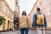 Back view of couple holding hands with backpack in city
