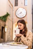 Selektivní zaměření ženy držící bílý šálek čaje v kavárně ve městě