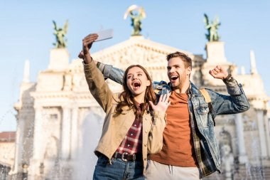 Excited couple taking selfie near fountain in city stock vector