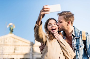 Selective focus of man kissing excited girlfriend taking selfie with smartphone stock vector