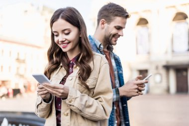 Woman and man smiling and chatting with smartphones