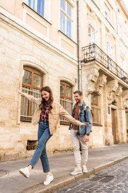 Couple having fun while walking on sidewalk in city stock vector