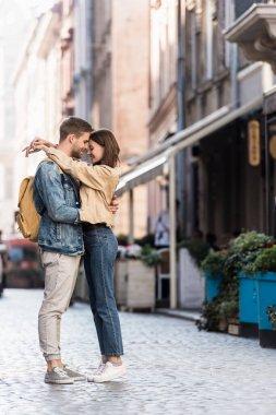 Happy boyfriend and girlfriend hugging in city stock vector