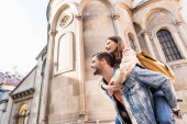 Low angle view of man piggybacking girlfriend near building in city