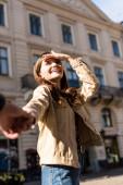 Zugeschnittene Ansicht Freundin und Freund Händchen haltend und lächelnd in der Stadt