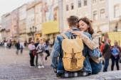 Přítel s batohem a přítelkyně se zavřenýma očima objímající a usmívající se ve městě