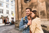 Selective focus of girlfriend and boyfriend looking away, holding hands and smiling near wall in city