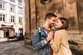 Man and woman holding hands, looking at each other and smiling near wall in city