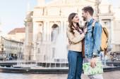 Pár se na sebe dívá, objímají se s mapou u fontány ve městě