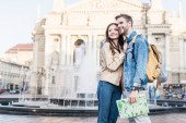 Pár se dívá jinam, objímají se a usmívají s mapou u fontány ve městě