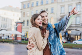 Man smiling, holding map, pointing with finger and hugging happy woman in city