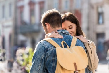 Girlfriend hugging boyfriend with beige backpack in city stock vector