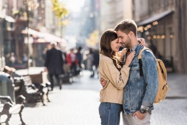 Boyfriend with hand in pocket and girlfriend hugging with closed eyes in city in Europe stock vector