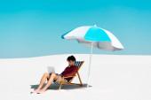 szabadúszó ül laptop fedélzet szék ernyő alatt homokos strandon ellen kék ég