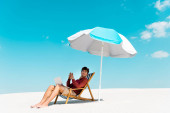 mosolygós szabadúszó ül laptop fedélzet szék alatt esernyő homokos tengerparton ellen kék ég
