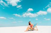 schöne sexy Mädchen in Badeanzug und Sonnenbrille sitzt im Liegestuhl am Sandstrand mit blauem Himmel und Wolken
