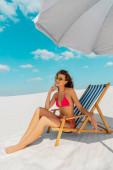 Fotografie usmívající se krásná sexy dívka v plavkách a slunečních brýlích sedí v lehátku pod slunečníkem na písečné pláži