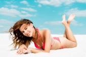 usmívající se krásná sexy dívka v plavkách ležící na písečné pláži s modrou oblohou a mraky na pozadí