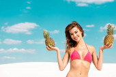 smiling beautiful sexy girl in swimsuit with pineapples on sandy beach with blue sky and clouds