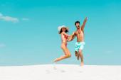 Lächelndes junges Paar springt gemeinsam am Sandstrand