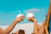 abgeschnittene Ansicht eines jungen Paares, das in Liegestühlen mit Kokosgetränken am Sandstrand sitzt