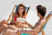 mosolygó fiatal pár ül fedélzeti székek kókuszos italok homokos strandon