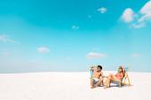 mosolygó fiatal pár ül fedélzeti székek és nézte félre homokos strandon