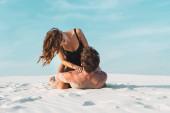 Fotografie sexy mladá žena sedí na přítele ležící na písečné pláži