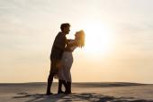boční pohled na mladé páry objímání na písečné pláži při západu slunce