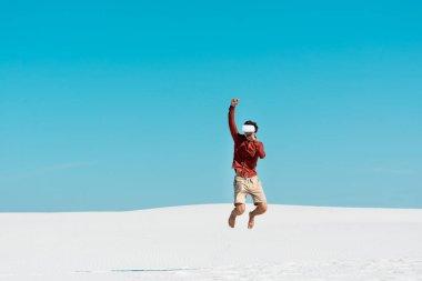 Kumlu sahilde, kulaklıklı bir adam açık mavi gökyüzüne doğru atlıyor.