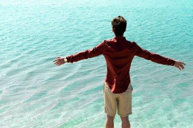 Turkuaz suda uzanan, uzanmış elleri olan adamın arka görüntüsü.