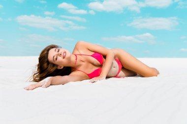 Gülümseyen, mayolu seksi kız kumlu sahilde uzanmış mavi gökyüzü ve arka planda bulutlar.