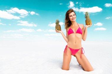 Gülümseyen, mayo giymiş, kumlu sahilde ananaslı, mavi gökyüzü ve bulutlu seksi bir kız.