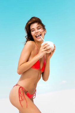 Kumsalda mayo giymiş, hindistan cevizi içecekleriyle gülümseyen seksi kız.