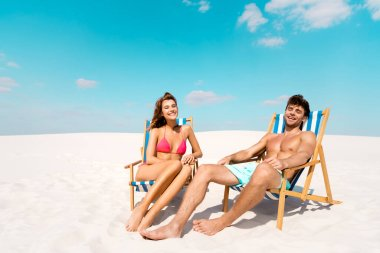 smiling young couple sitting in deck chairs on sandy beach