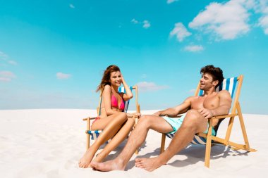 Smiling young couple sitting in deck chairs on sandy beach stock vector