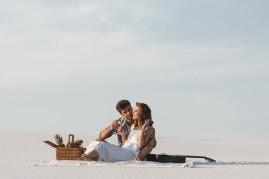young couple drinking champagne while sitting on blanket with basket of fruits and acoustic guitar on beach