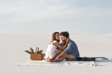 young couple embracing while sitting on blanket with basket of fruits and acoustic guitar on beach