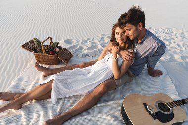 young couple hugging while sitting on blanket with basket of fruits and acoustic guitar on beach