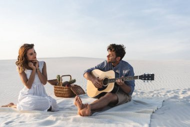 man playing acoustic guitar to girlfriend near wicker basket with fruits on beach