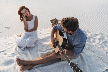 man playing acoustic guitar to girlfriend on beach