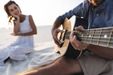 selective focus of man playing acoustic guitar to girlfriend on beach