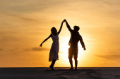 Photo silhouettes of man and woman dancing on beach against sun during sunset
