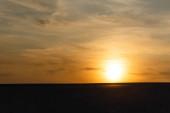 tmavá písečná pláž proti jasnému slunci při západu slunce
