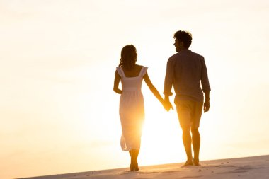 Silhouettes of man and woman holding hands while walking on beach against sun during sunset stock vector